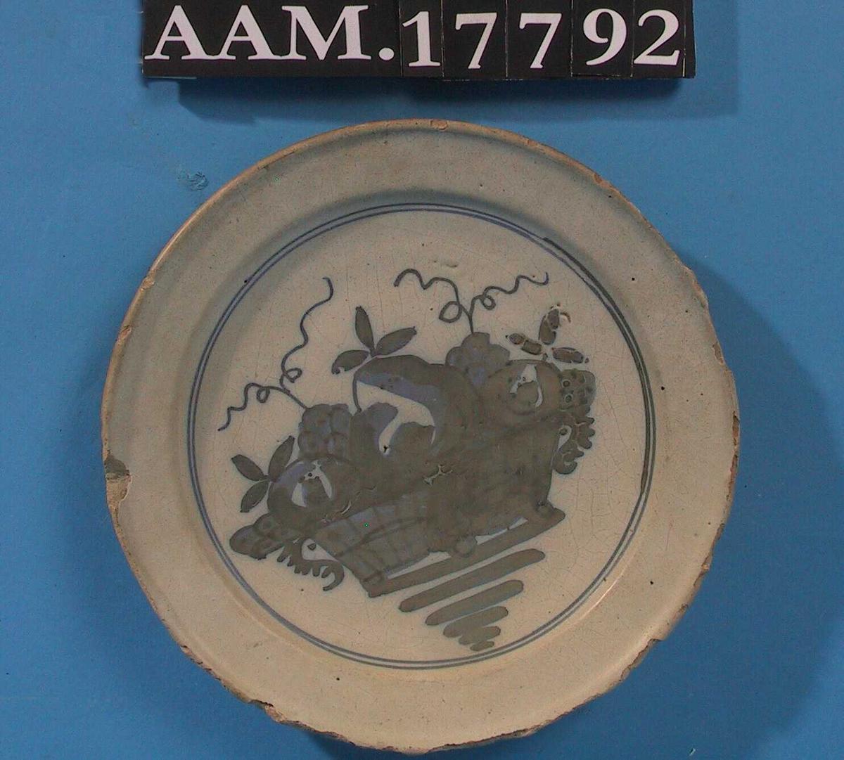 Rundt kanten  av speilet to tynne blå ringer.  I speilet et motiv som fyller hele:   vase  med   frukt,  en   pære  pm. med et   eple  på hver side. Under kurven blå streker  paralelle, ned i en spiss.