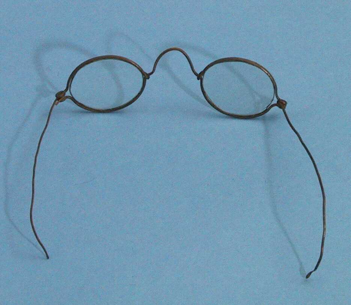 Enkle briller, brilleglassene er små, omfatningen er laget av ståltrådliknende materiale og lett bøyelig.