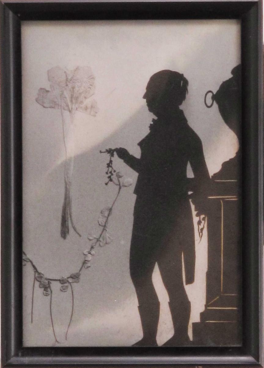 Portrett i helfigur. Stående mann, i profil,  holder en blomsterguirlander i hånden, Bak ham t.h. en klassisk urne e.l. på en sokkel.