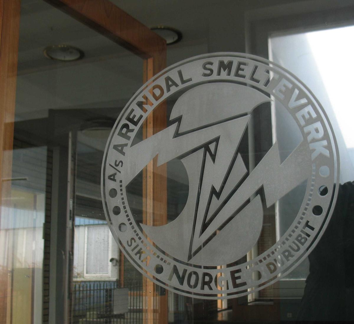 Arendal Smelteverk, kontorbygningen. Dør med innslipt logo.