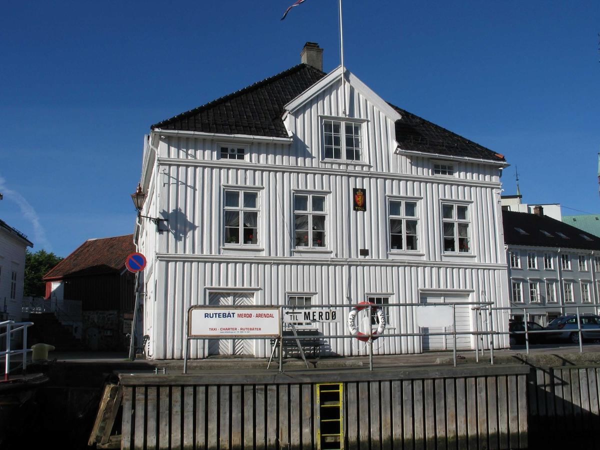 Den gamle Tollboden på Tyholmen, fasade mot Pollen. Fotografert fra merdøbåten. Tollskilt er igjen montert på veggen.