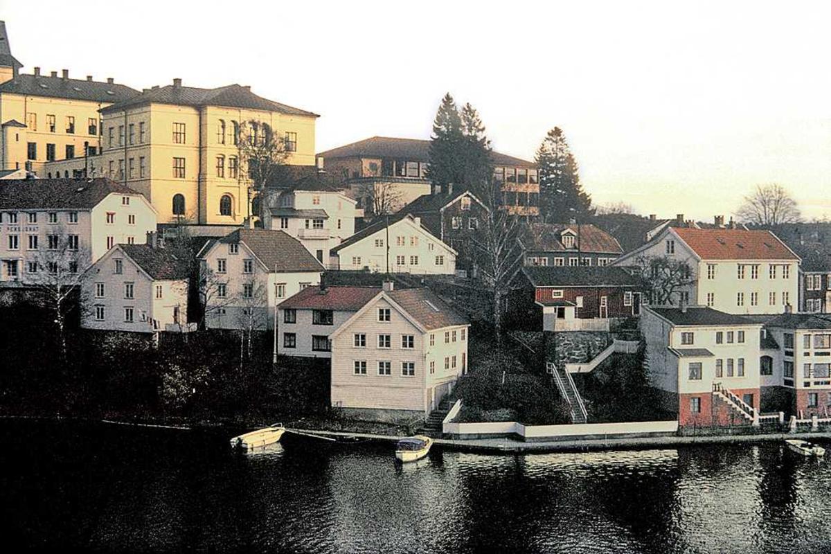 Bebyggelse på Tyholmens SV-side, sett fra Vesterveien e.l. Skolebygningen øverst t.v. i bildet, bebyggelsen mot Kittelsbukt i forgrunnen. Skolens nybygg sees bak den gamle bebyggelsen.