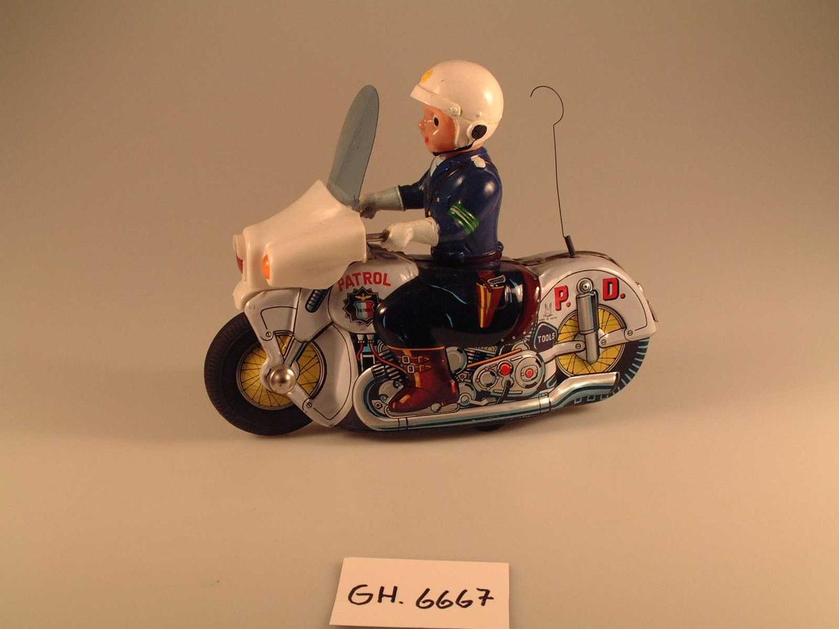 Politimann med hjelm sittende på motorsykkel. På undersiden to gummihjul. Når man skyver sykkelen fremover, overfører hjulene kraft til innvendig mekanisme, som driver sykkelen videre fremover.