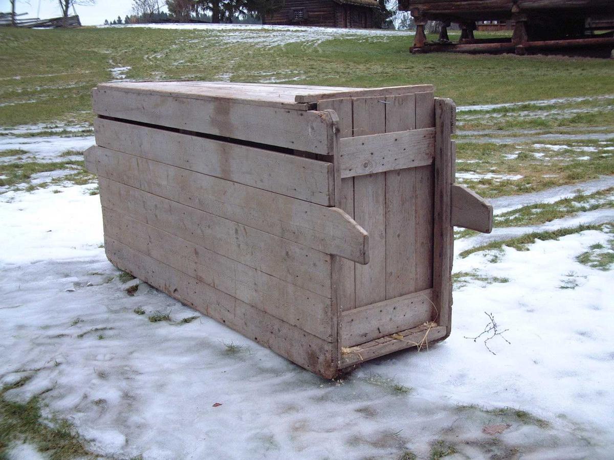 Firkantet kasse med tette vegger, bunn og tak. Seks vannrette planker i hver av langveggene. I begge ender er to av plankene er forlenget til håndtak. Hver av endevegger består av fire loddrette planker holdt sammen av to tverrstykker. Begge endeveggene kan heves og senkes for å slippe grisen inn/ut. Tak av fire planker.