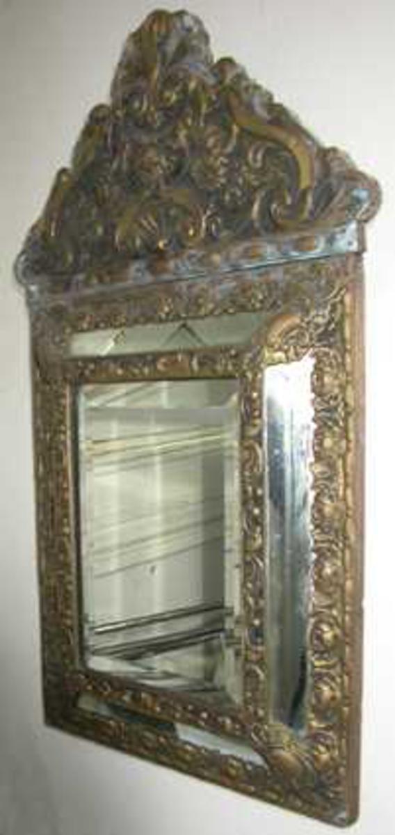 Speil, lite veggspeil, ramme i gult metall med blomstermønster, firkantet med trekantet gavlstykke. Midtspeil står ut fra veggen, kranses av fire smale og skråtstilte sidespeil.