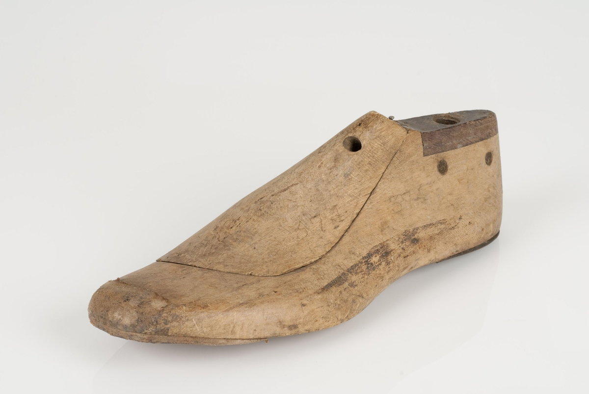 En tremodell i to deler; lest og opplest/overlest (kile). Venstrefot i skostørrelse 38, og 6 cm i vidde. Hælstykket av metall. Lestekam av skinn