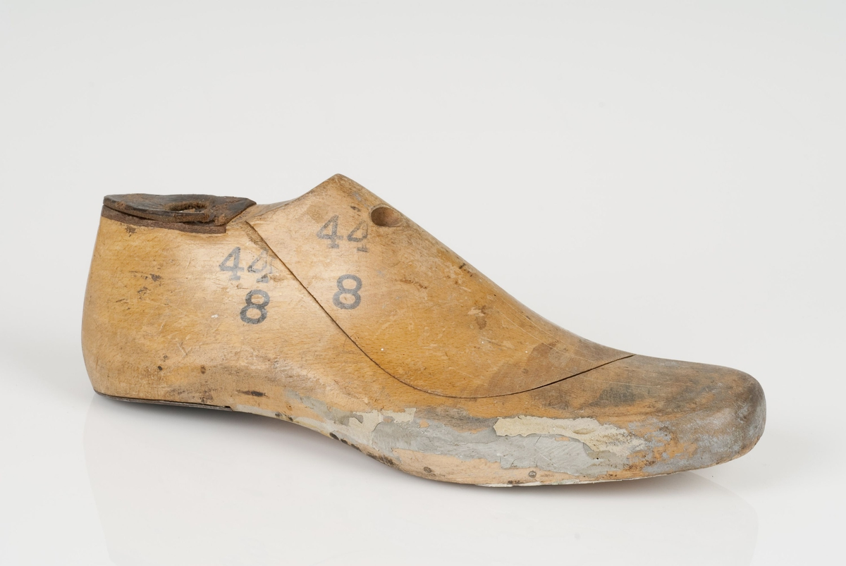 En tremodell i to deler; lest og opplest/overlest (kile). Høyrefot i skostørrelse 44, og 8 cm i vidde. Hælstykket i metall. Lestekam i skinn.