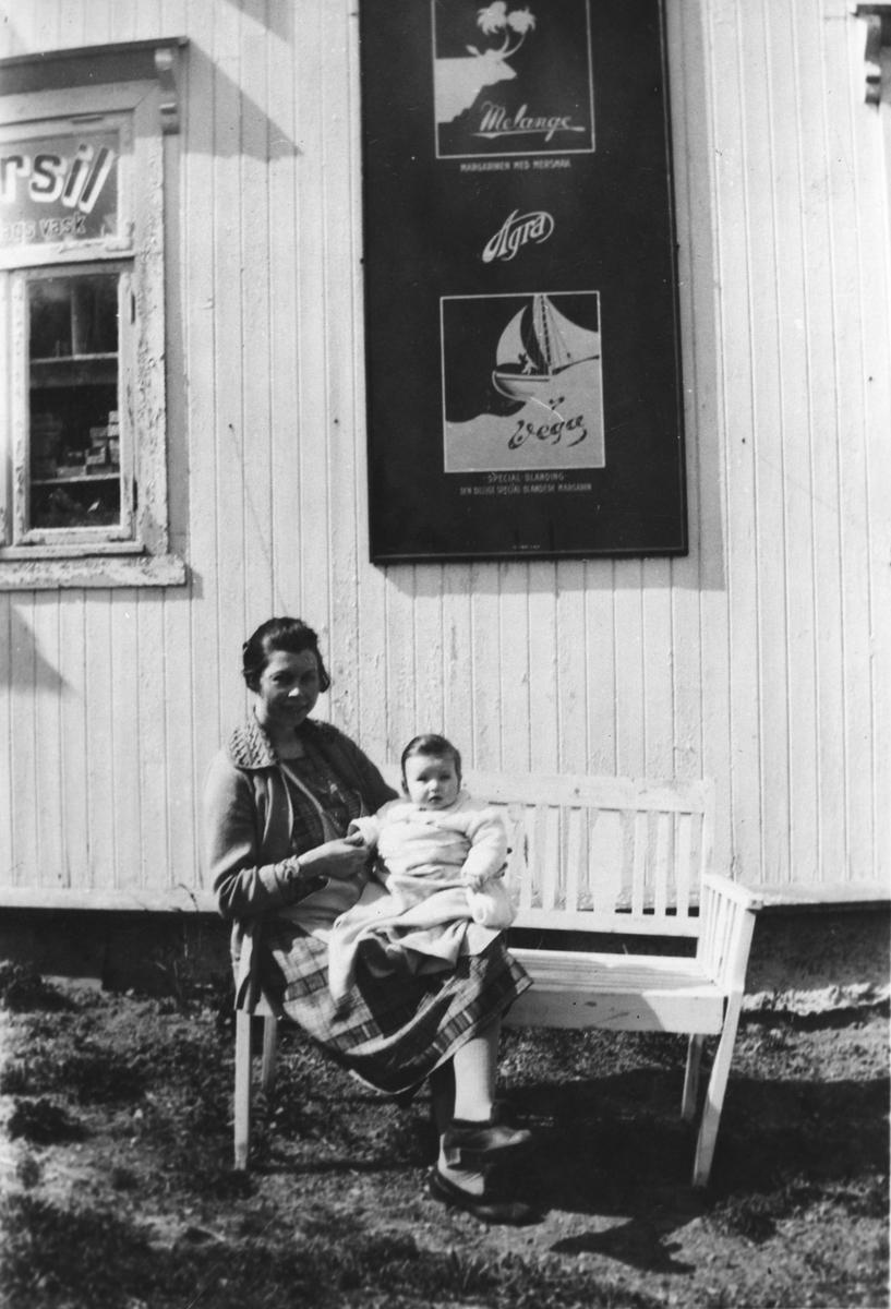Mor med spebarn på fanget, sittende på krakk foran landhandel.