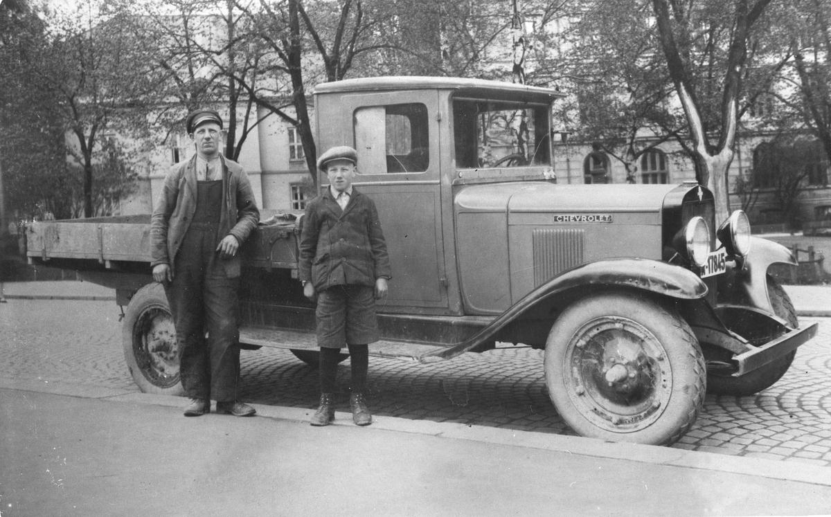 Mann og gutt ved lastebil i bygate
