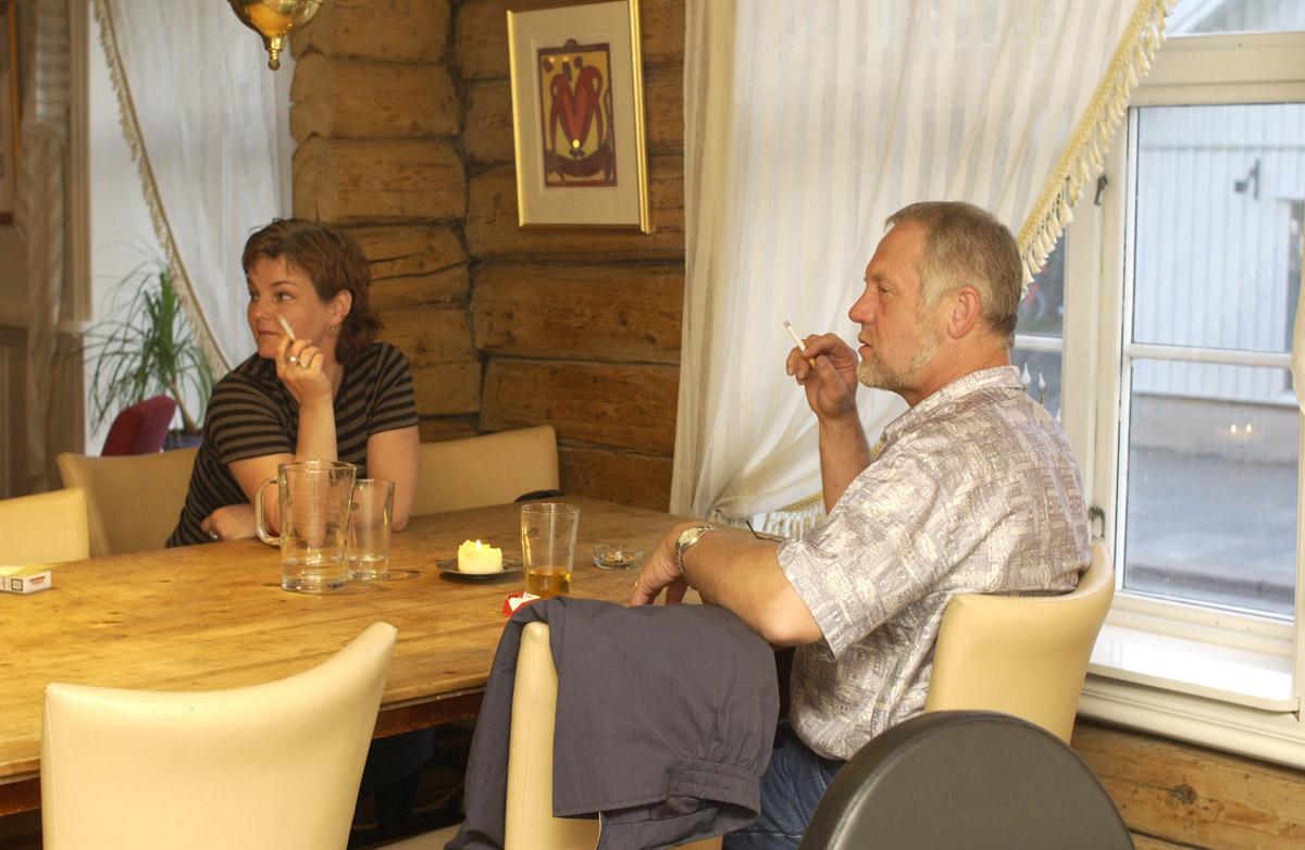 Mann og kvinne med sigaretter ved et bord, Jungeltelegrafen, Drøbak.