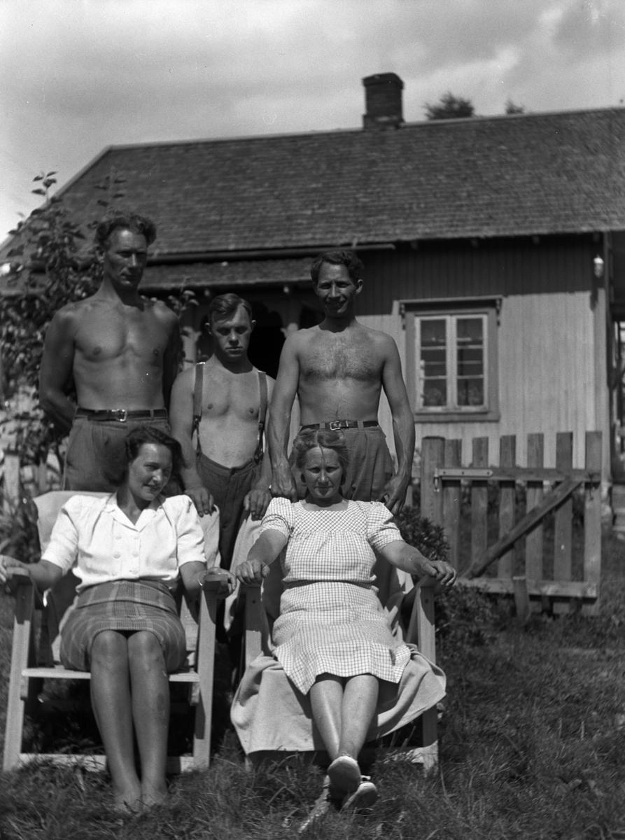 Ukjente kvinner og menn i en hage foran et hus.