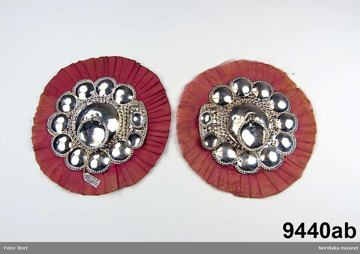 """Huvudliggaren (år 1875): """"9.440 Ett par bröstspännen fr. Löderups sn. Ingelstads hd. Skåne. Från Hagestads by. Ink. ss. 9,437 [= gm. skomakaren M. Hansson jämte 9,435 - 9455 - 108 kr.].""""  a-b) Spänne, av silver, tvådelat. Varje halva i det närmaste rund, av pressad silverplåt med en större buckla i mitten omgiven av mindre bucklor samt små stjärnor mellan dessa. Mitt på varje halva, fäst i en ögla, ett stort, runt skålat löv med pressad/punsad kantdekor. På halvornas insida en avvikande dekor med på var halva två små, hängande, runda, skålade löv. På baksidorna åldermansrankor och på ovansidorna en otydlig mästarstämpel slagen två gånger på varje halva. Tidigare tolkas som NI (Nils Juhlin, Karlshamn), men kan även vara HI, HF eller HT. Möjligen Hans Fick, verksam i Kristianstad 1797-1822 (1824). Varje halva är monterad på rött kläde med kant av veckat siden. Diameter 15 cm. Blekt. /Marie Tornehave 2008-12-09"""